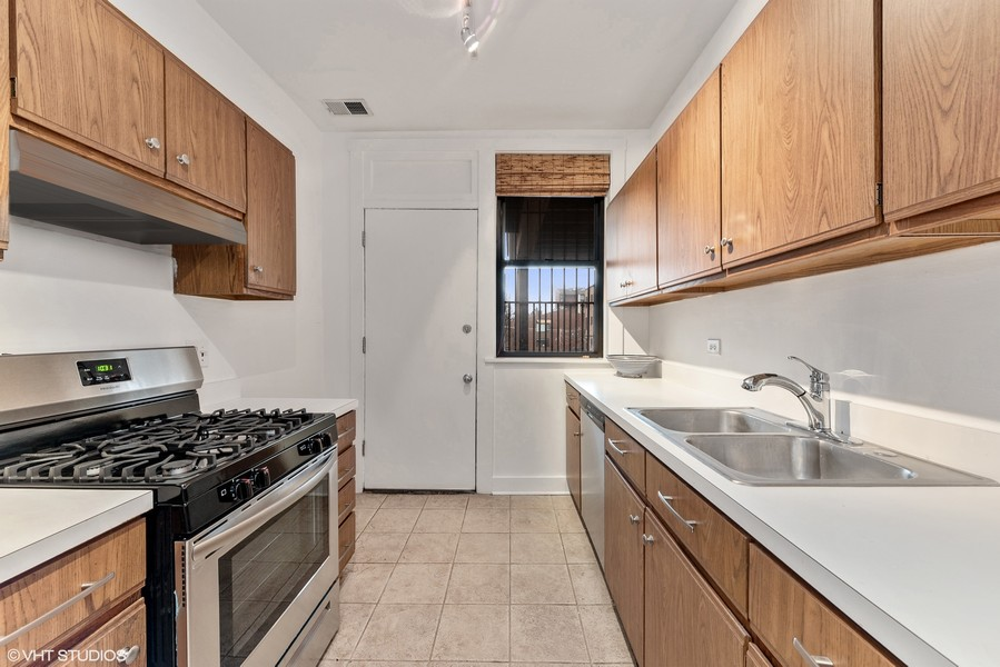 Real Estate Photography - 3723 N Pine Grove #3N, Chicago, IL, 60613 - Kitchen with Door to Back Deck for Grilling