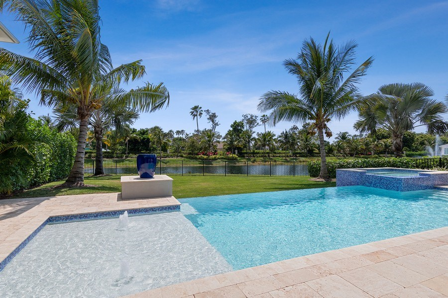 Real Estate Photography - 6888 Leeward Way, Naples, FL, 34109 - Giant green waterfront lawn with Coconut Palms