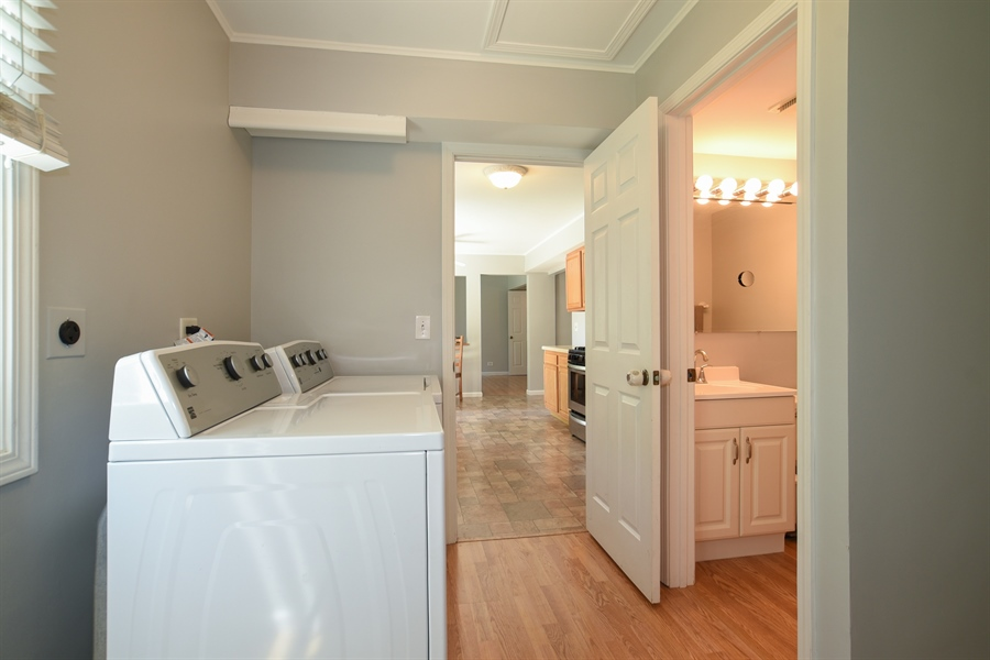 Real Estate Photography - 2021 Briar Hill Drive, Schaumburg, IL, 60194 - Laundry Room with Storage and Half Bath off Kitche