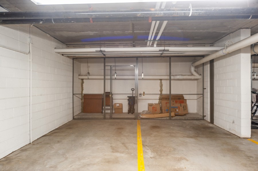 Real Estate Photography - 400 Village Green Pkwy, 304, Lincolnshire, IL, 60069 - 2 Side x Side Garage Spaces with Storage