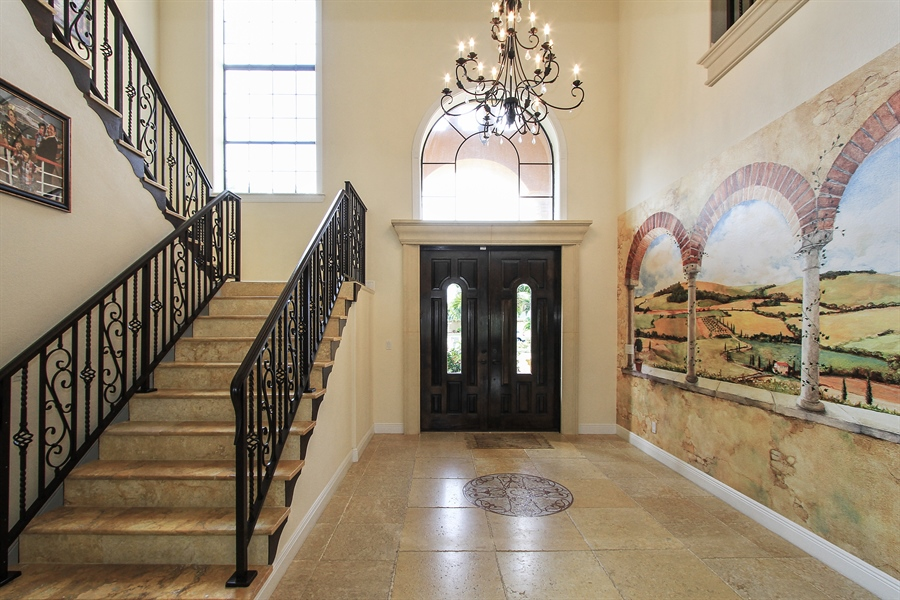 Real Estate Photography - 1930 SE 21st Ter, Cape Coral, FL, 33990 - Elegant foyer entrance with grand staircase