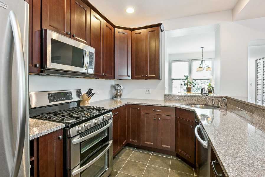 Real Estate Photography - 4822 N Winchester, 1N, Chicago, IL, 60625 - Renovated kitchen with fantastic breakfast bar
