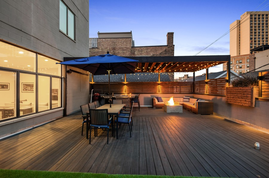 Real Estate Photography - 1113 N Ashland Ave, Unit 3, Chicago, IL, 60622 - Deck at dusk, built in fire-pit