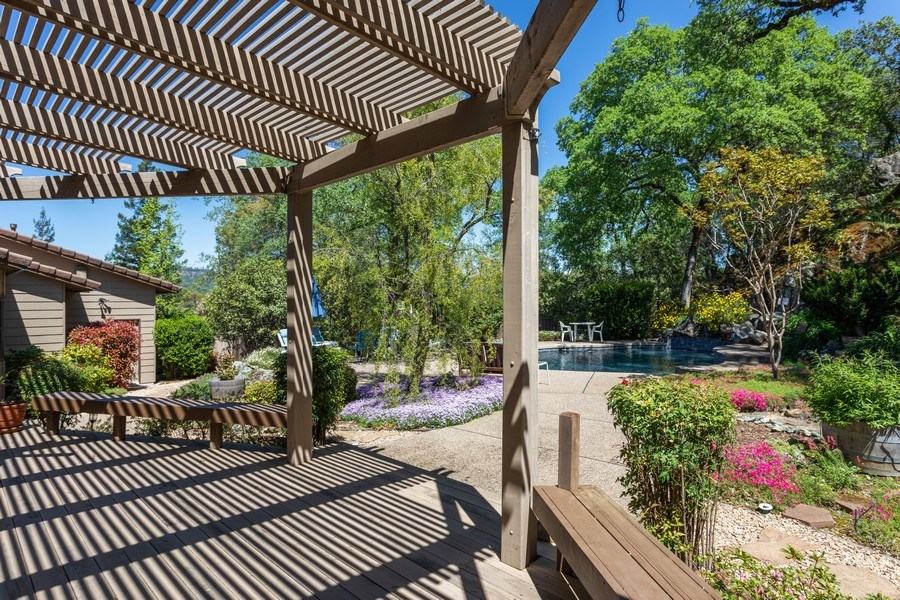 Real Estate Photography - 3570 Skyview Dr, Auburn, CA, 95602 - shaded deck overlooking the lovely yard and pool.