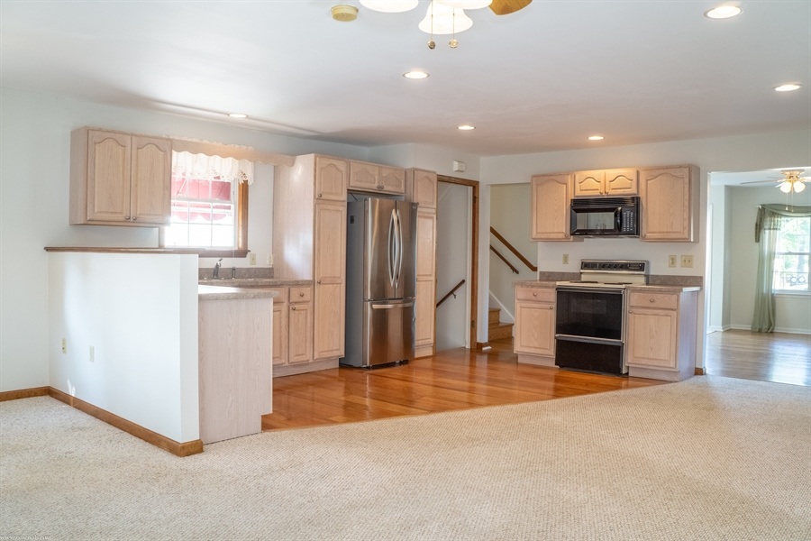 Real Estate Photography - 108 Rolling Dr, Newark, DE, 19713 - Kitchen with hardwoods, open to Family Room