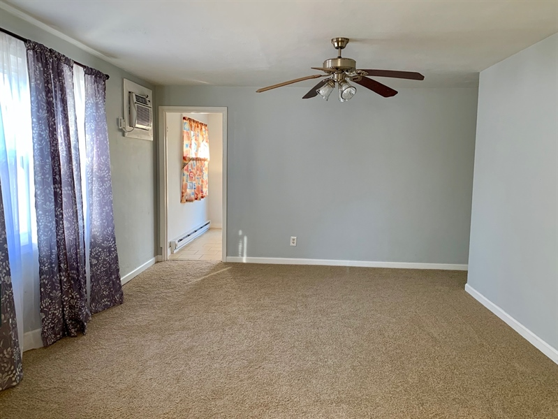 Real Estate Photography - 309 Howell Dr, New Castle, DE, 19720 - Living Room with new Carpet into Kitchen