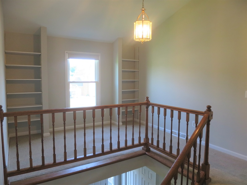 Real Estate Photography - 121 Brandywine Dr, Dover, DE, 19904 - Den with bookshelves at the top of the stairs