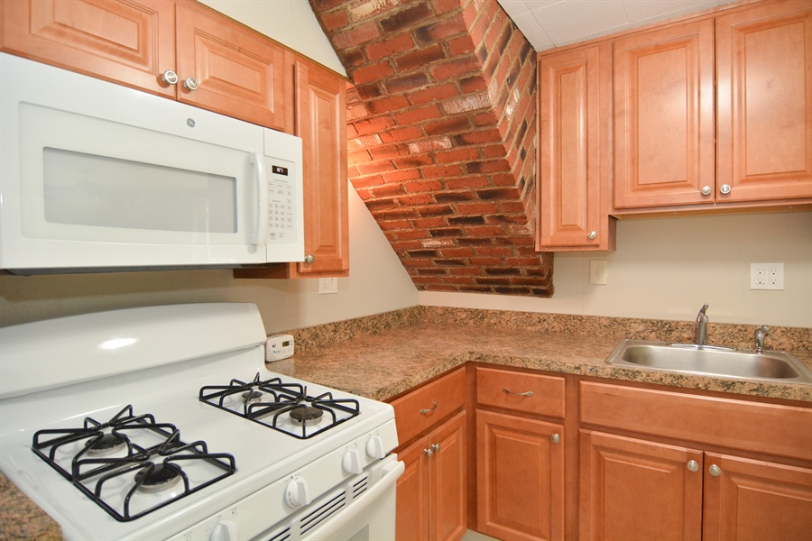 Real Estate Photography - 178 Wiltshire Rd, Claymont, DE, 19703 - Updated kitchen with warm, stylish brick accents