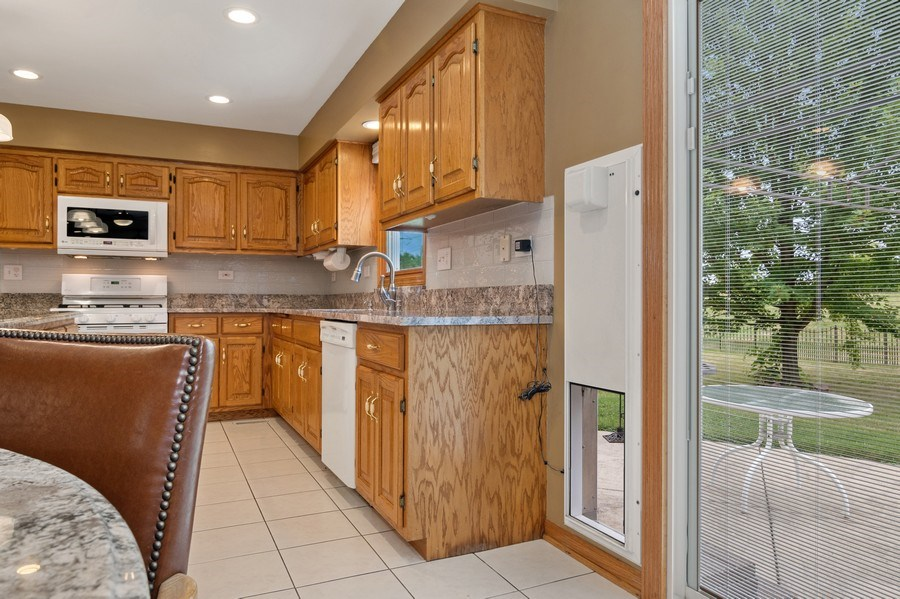 Real Estate Photography - 22W155 Glenrise Ct, Glen Ellyn, IL, 60137 - Kitchen with electronic pet door open